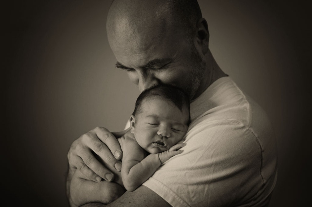 newborn in fathers arms