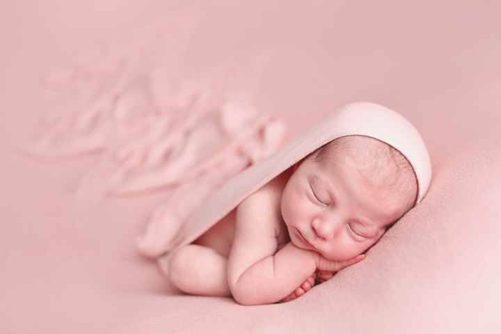 Newborn-girl-on-pink-backdr