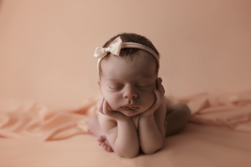 Newborn girl on peach backdrop in froggy pose