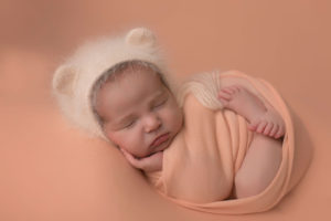 newborn-girl-in-peach-bear-bonnet