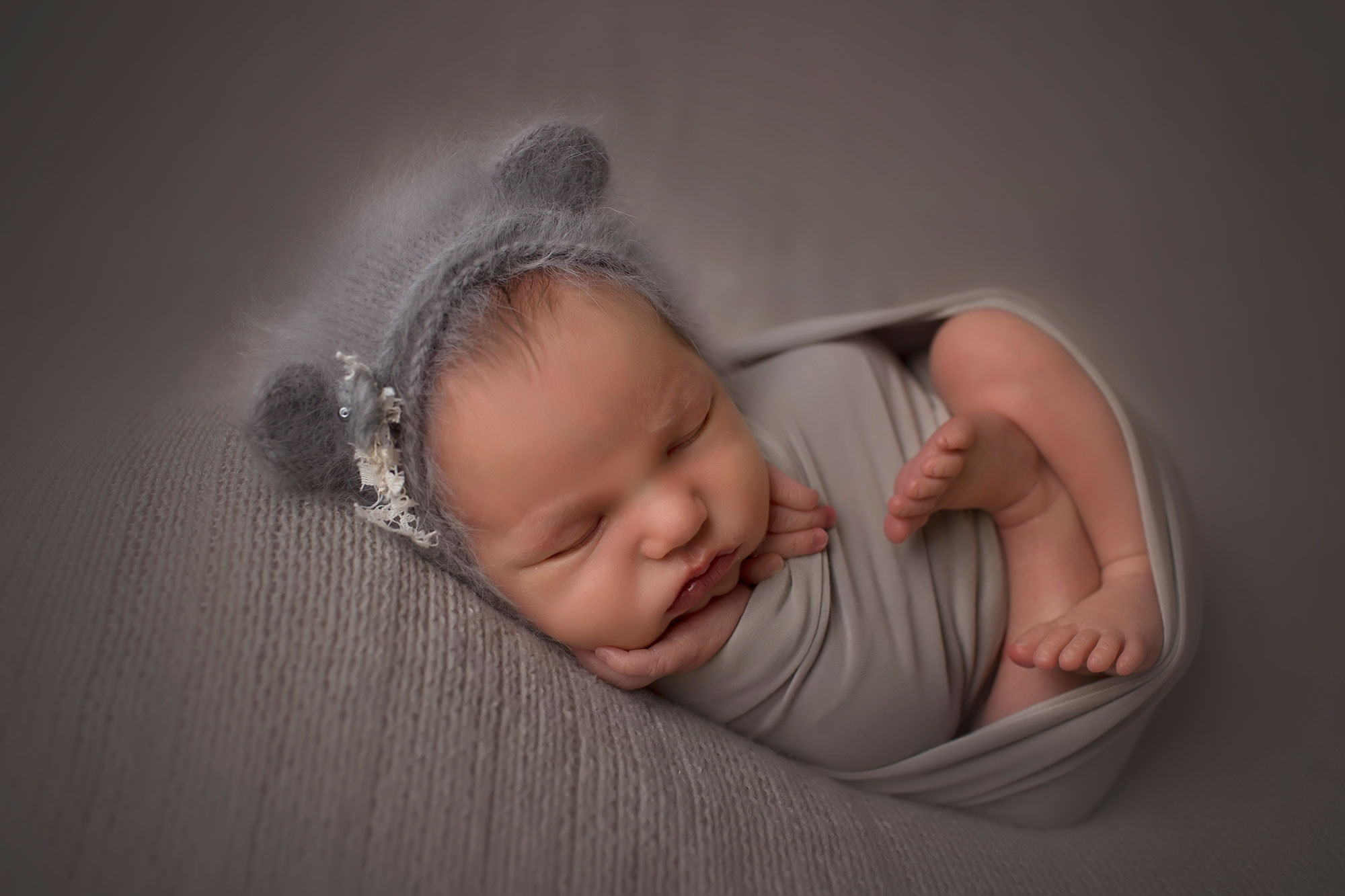 newborn-girl-in-gray-wrap-and-bear-bonnet