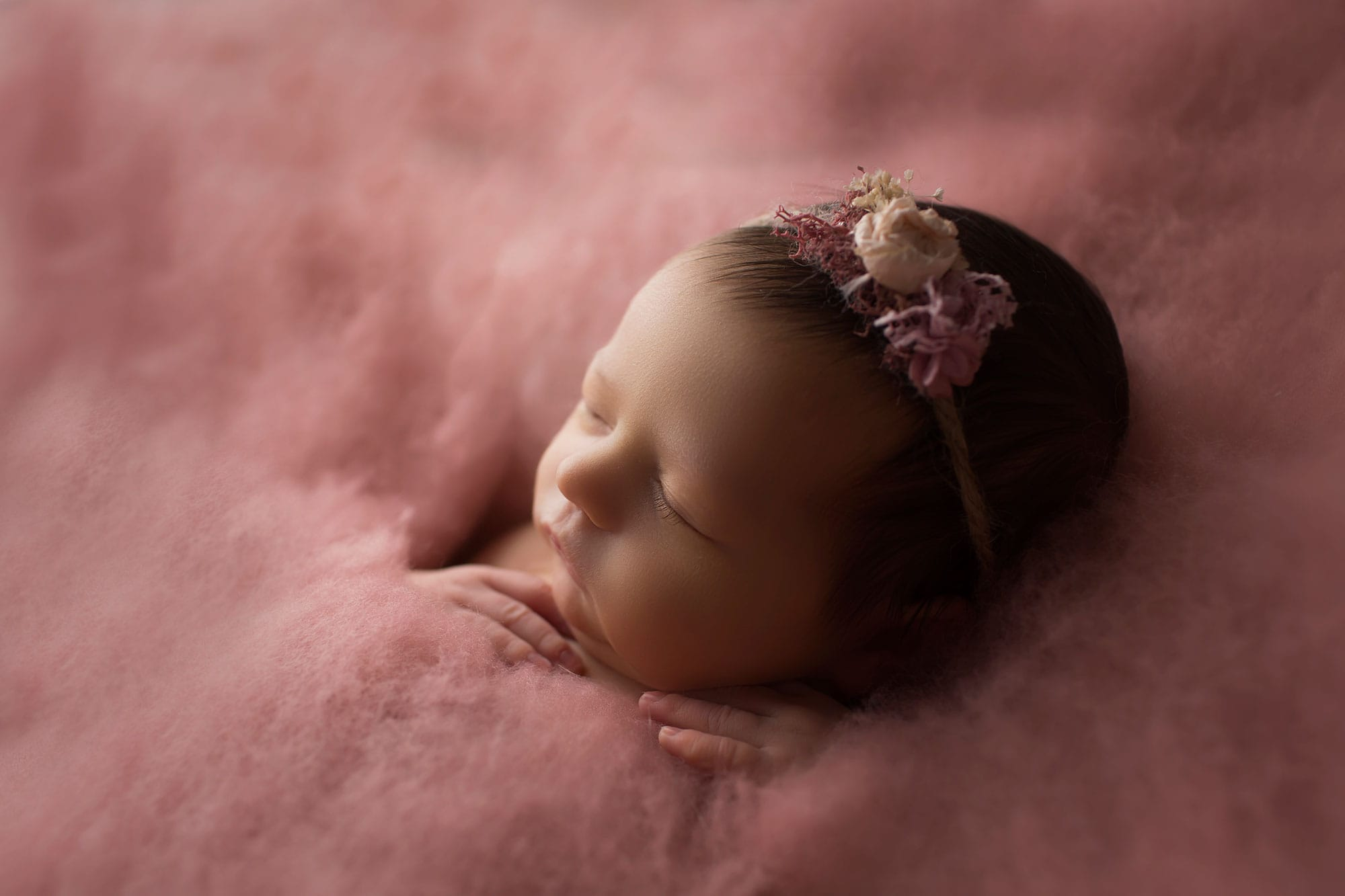 newborn girl on rose colored fluff