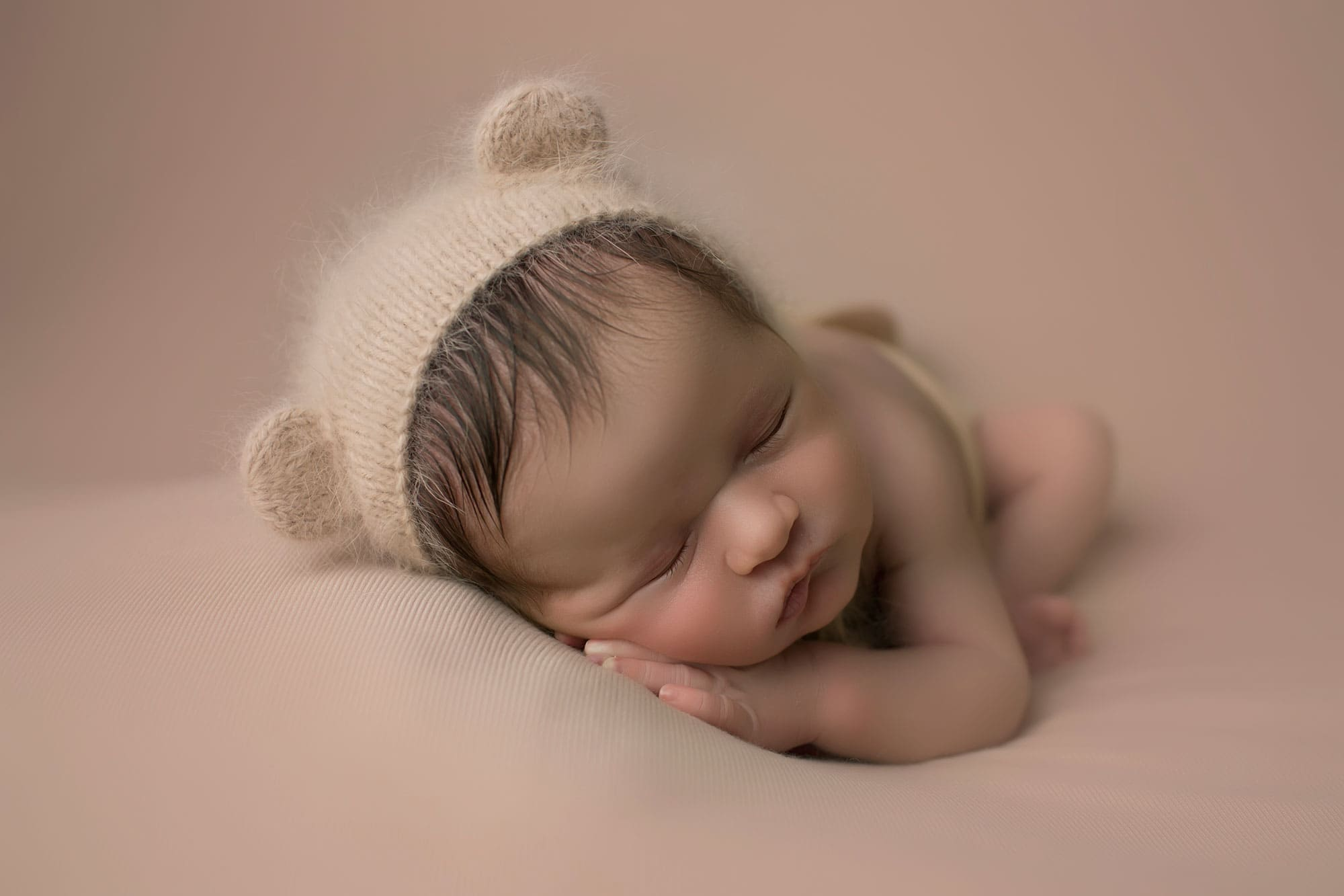 newborn boy on tan backdrop
