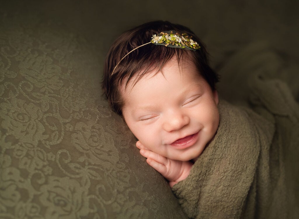 smiling newborn girl on green set up