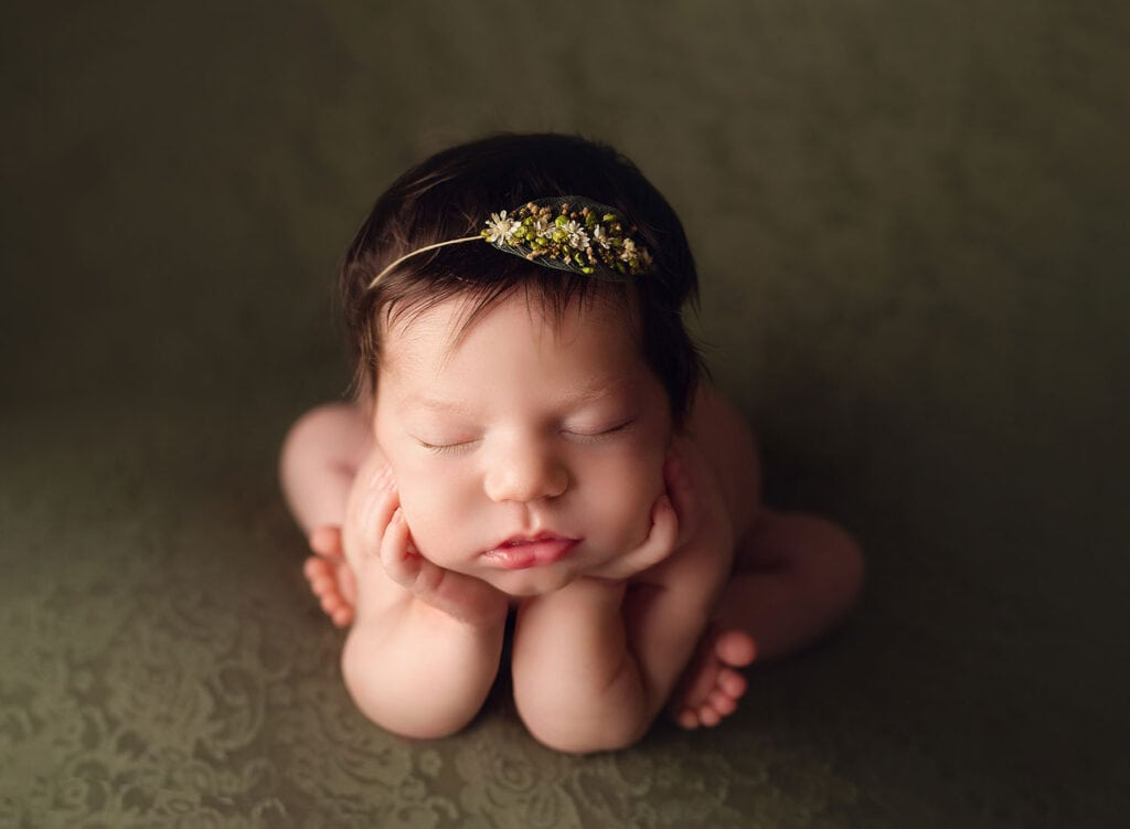 newborn girl on green backdrop