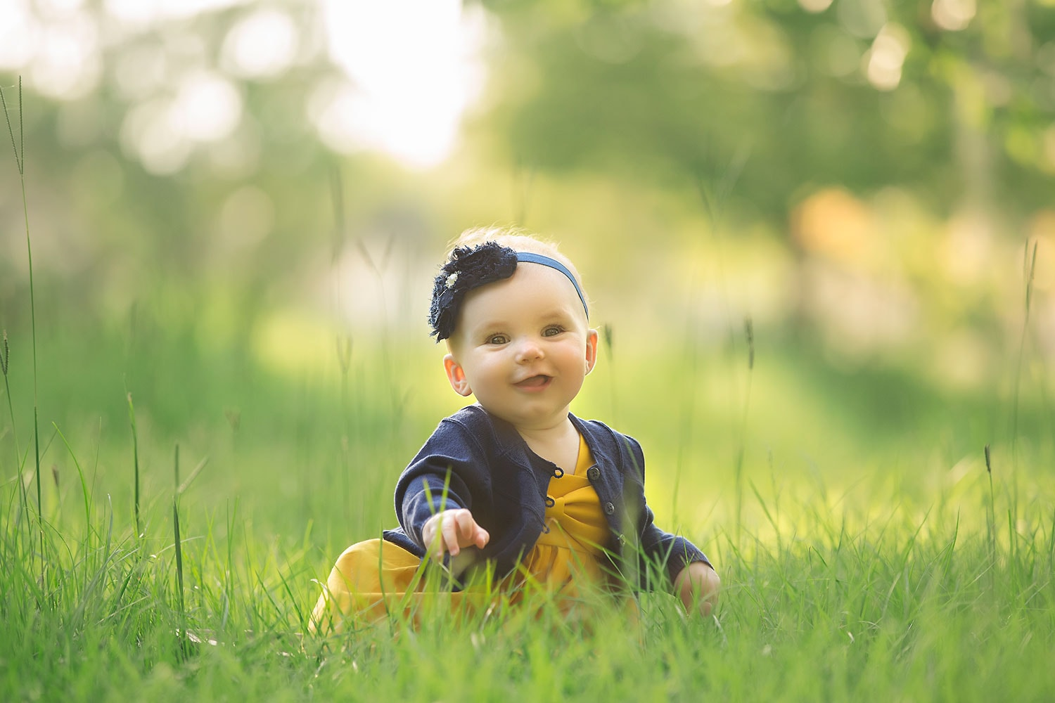 Six month old girl in tall grass by Annie Whitaker Photography
