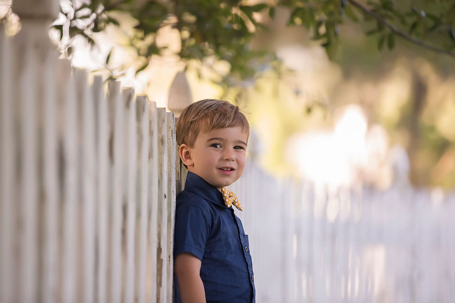 Boy standing by white picket fence by Annie Whitaker Photography