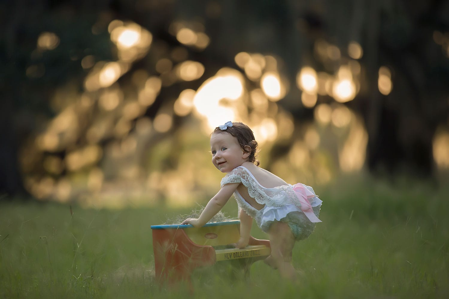 baby girl with piano at sunset by Annie Whitaker Photography