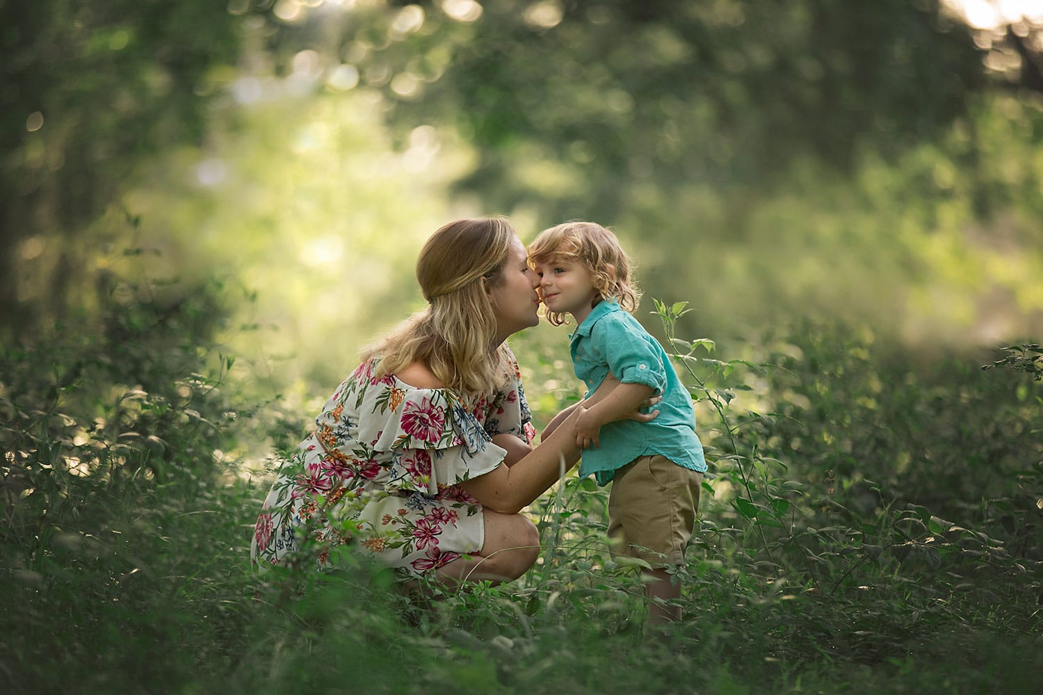 Little boy kissing mom in forest by Annie Whitaker Photography