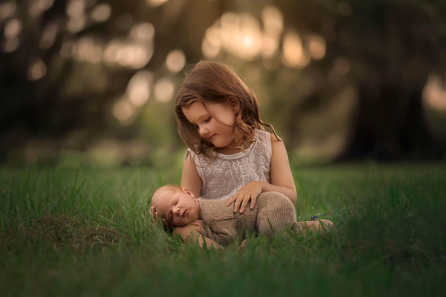 Big sister cradling brother by Annie Whitaker Photography