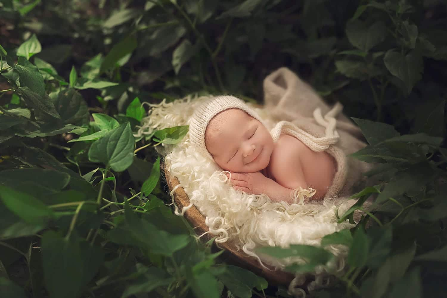 Smiling newborn outside by Annie Whitaker Photography