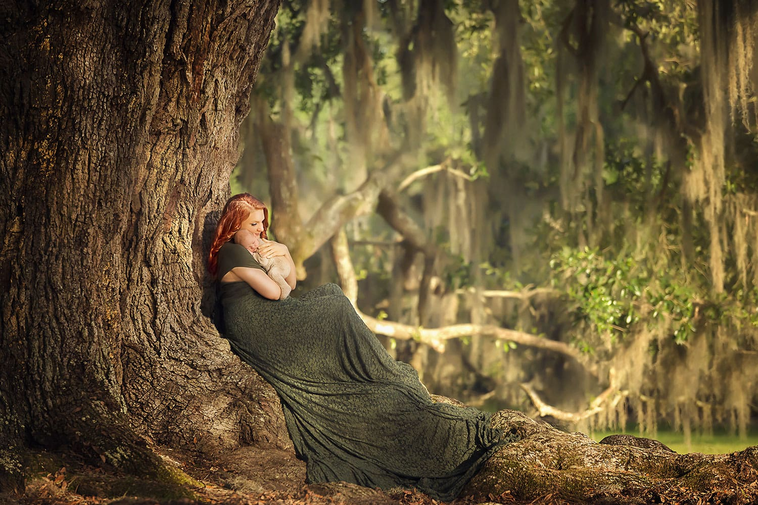 Stunning photo of mother holding newborn sitting in tree by Annie Whitaker Photography