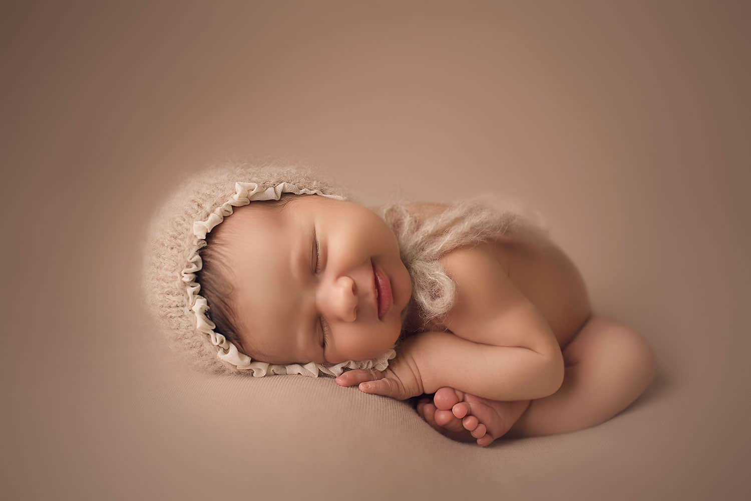 Smiling newborn in taco pose by Annie Whitaker Photography