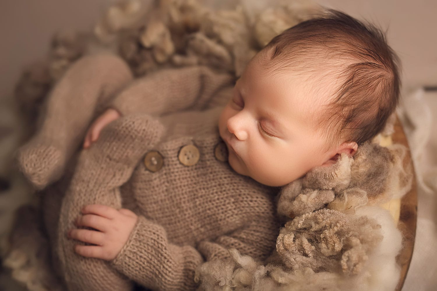 baby boy curled up on fluff by Annie Whitaker Photography