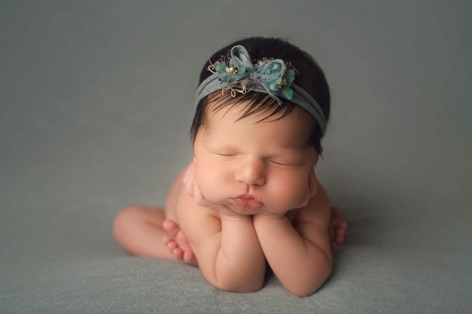 Newborn gril in froggy pose on greyish blue backdrop by annie Whitaker PHotography