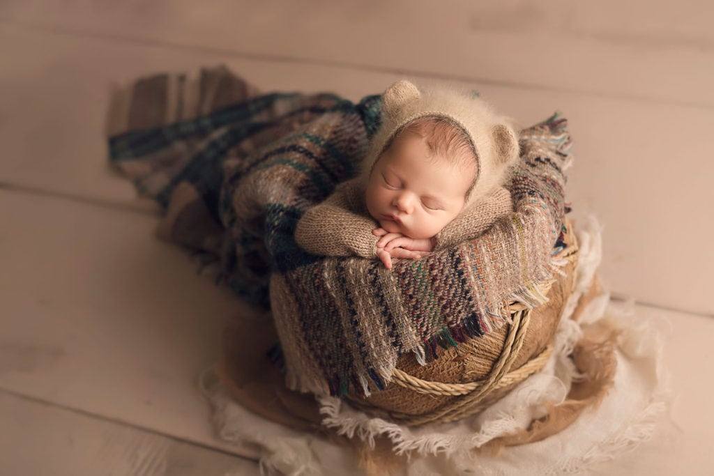 Adorable newborn baby boy in basket wearing bear bonnet by Annie Whitaker Photography