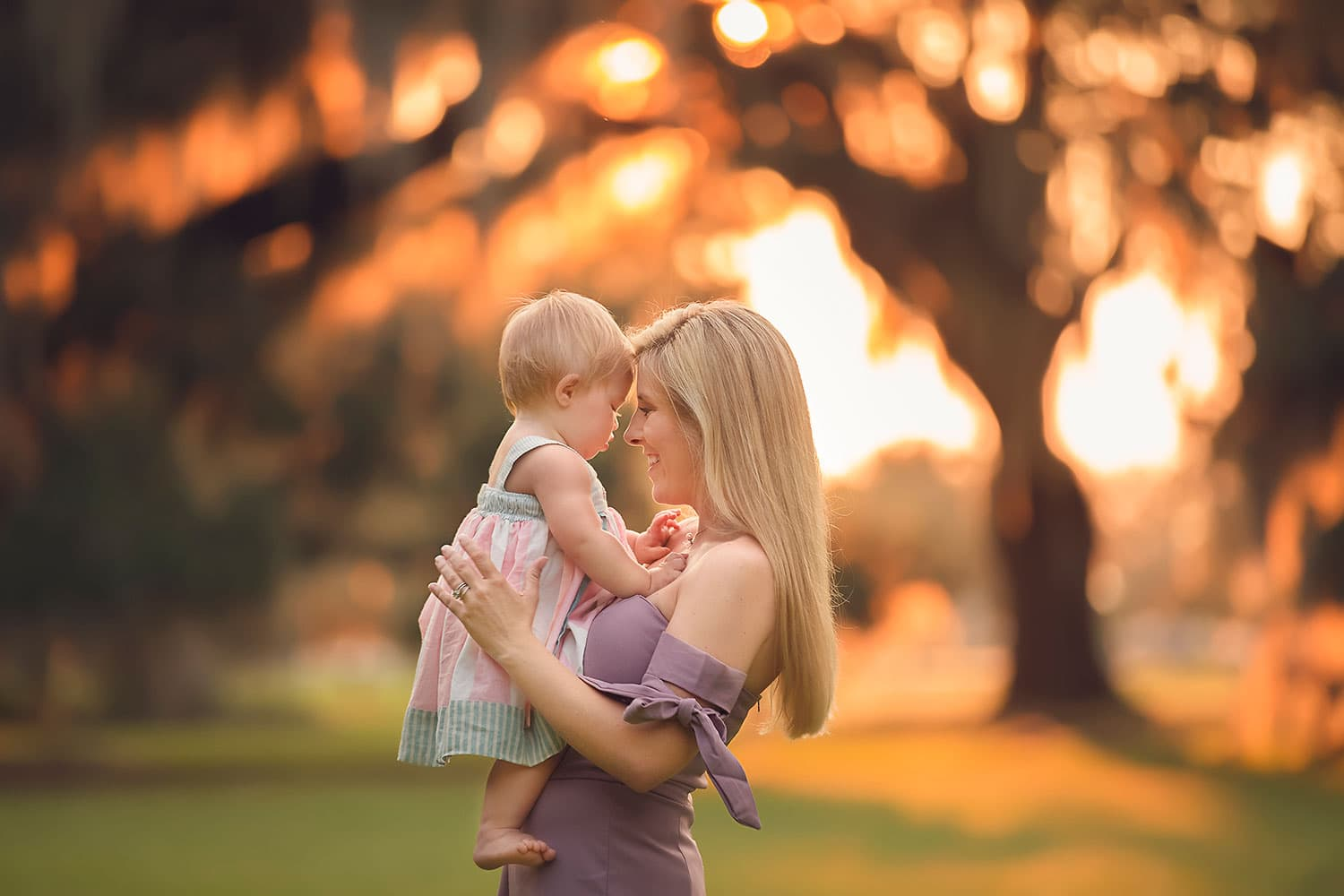 Mother and daughter snuggling at sunset by Annie Whitaker Photography