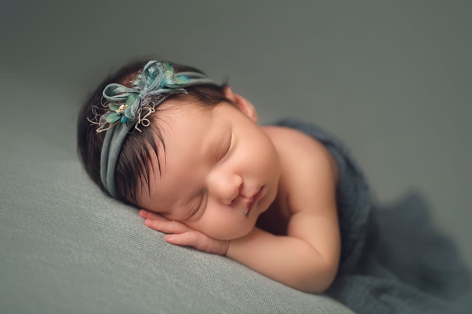 Dark-haired newborn girl sleeping by Annie Whitaker Photography