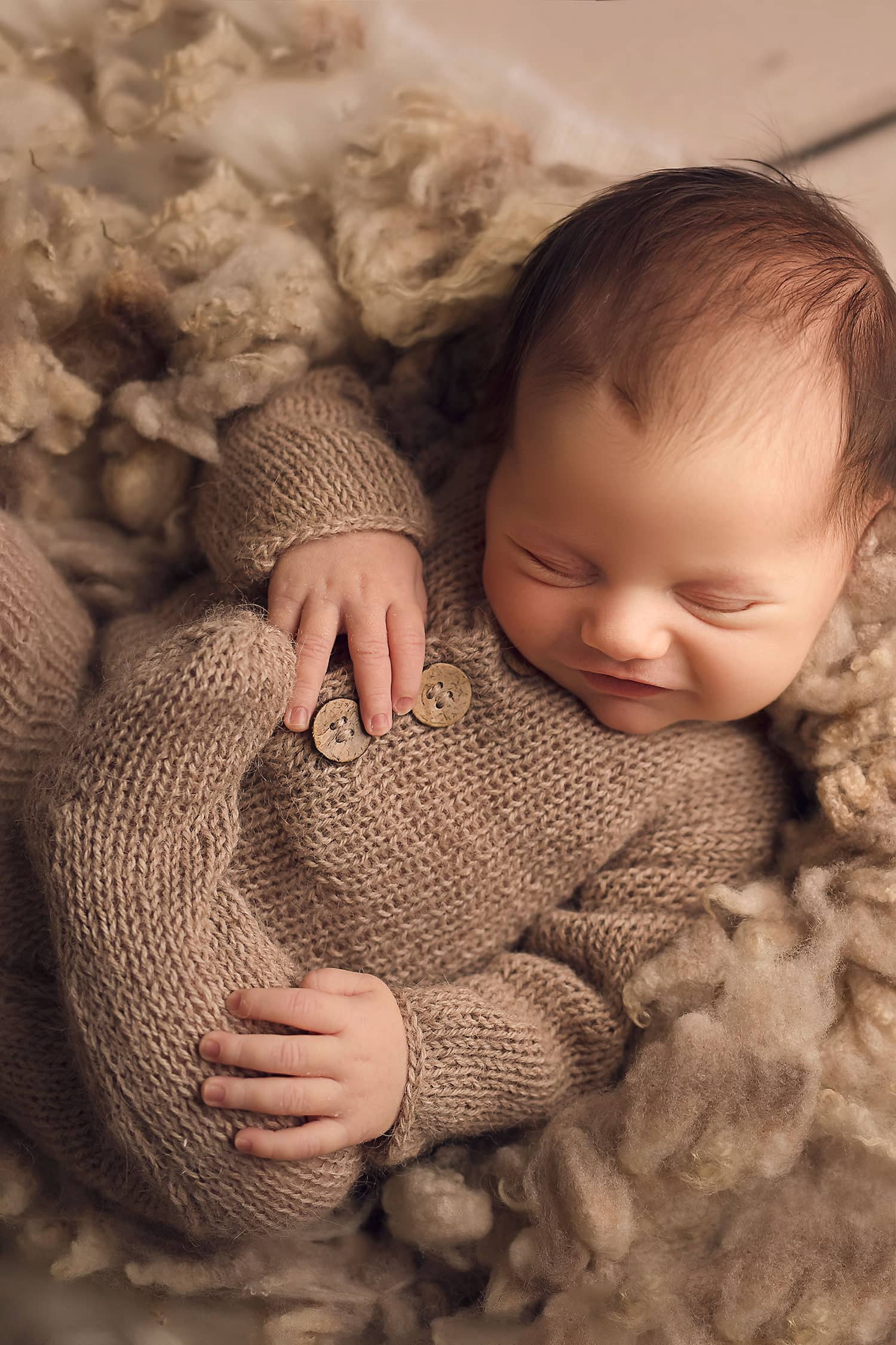 Newborn boy in tan knits smiling by Annie Whitaker Photography