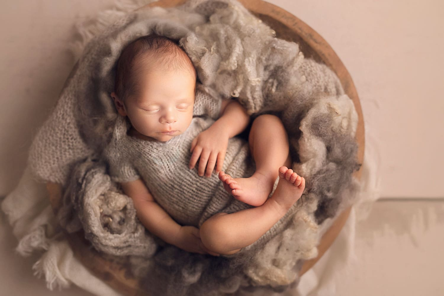 Baby boy in grey romper in bowl of grey fluff by Annie Whitaker Photography