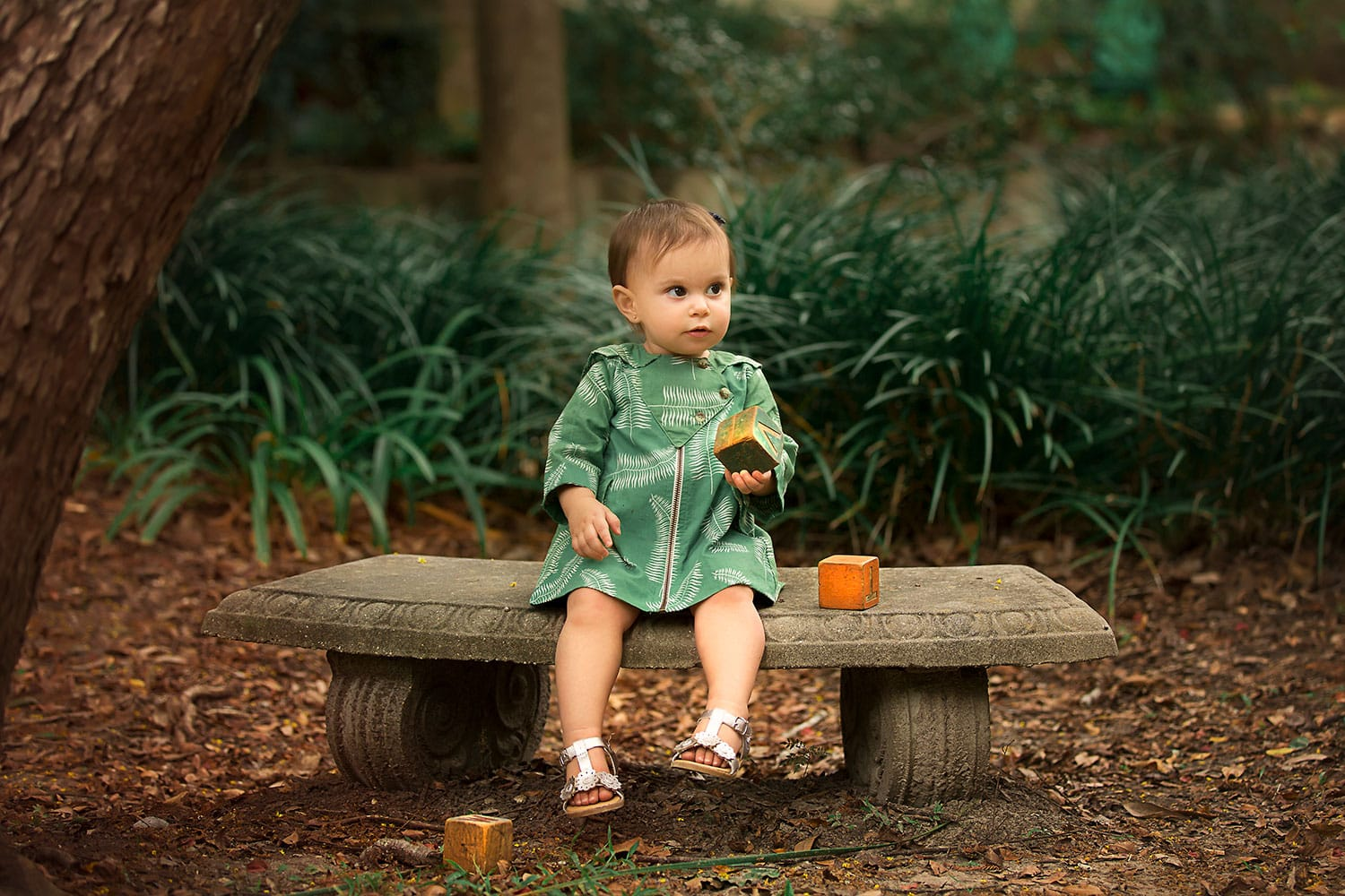 Baby girl sitting on little bench by Annie Whitaker Photography