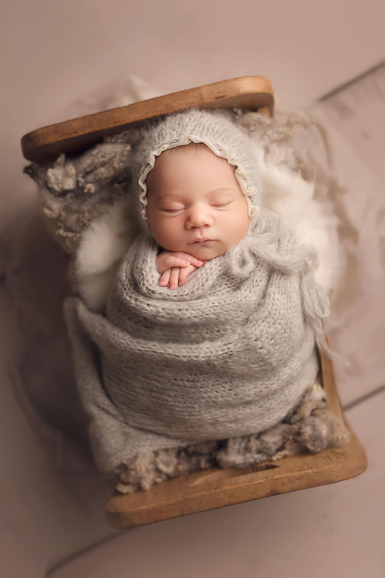 baby in tiny bed by Annie Whitaker Photography