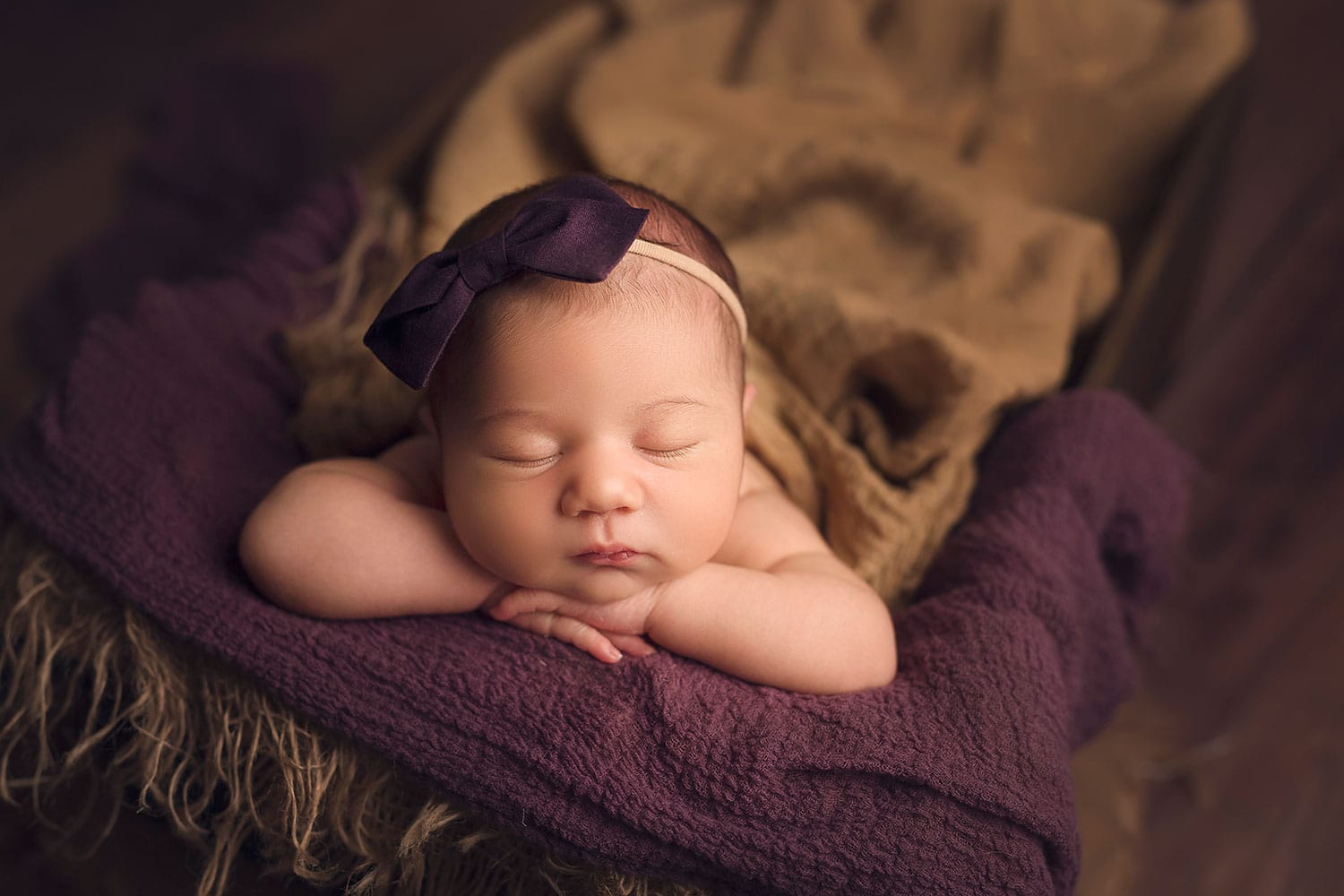 Baby girl with plum colored bow by Annie Whitaker Photography