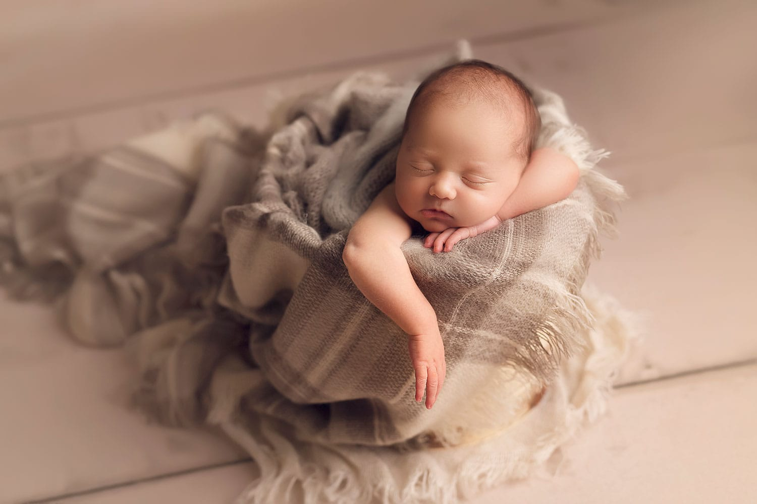 Newborn boy in bucket with dangling arm by Annie Whitaker Photography