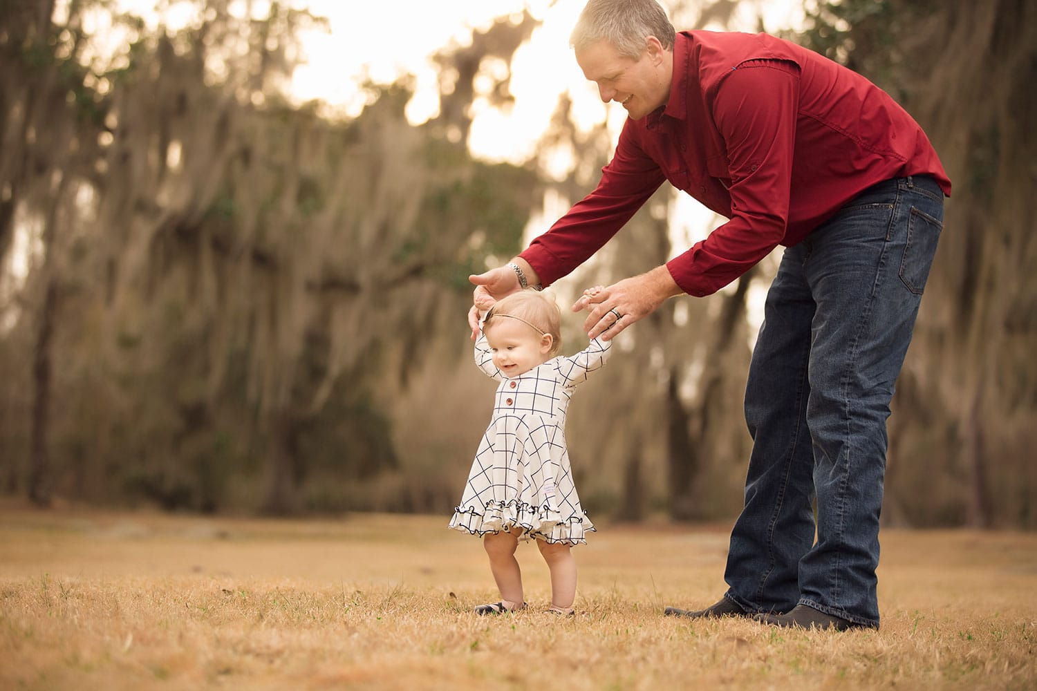 Dad helping baby walk by Annie Whitaker Photography