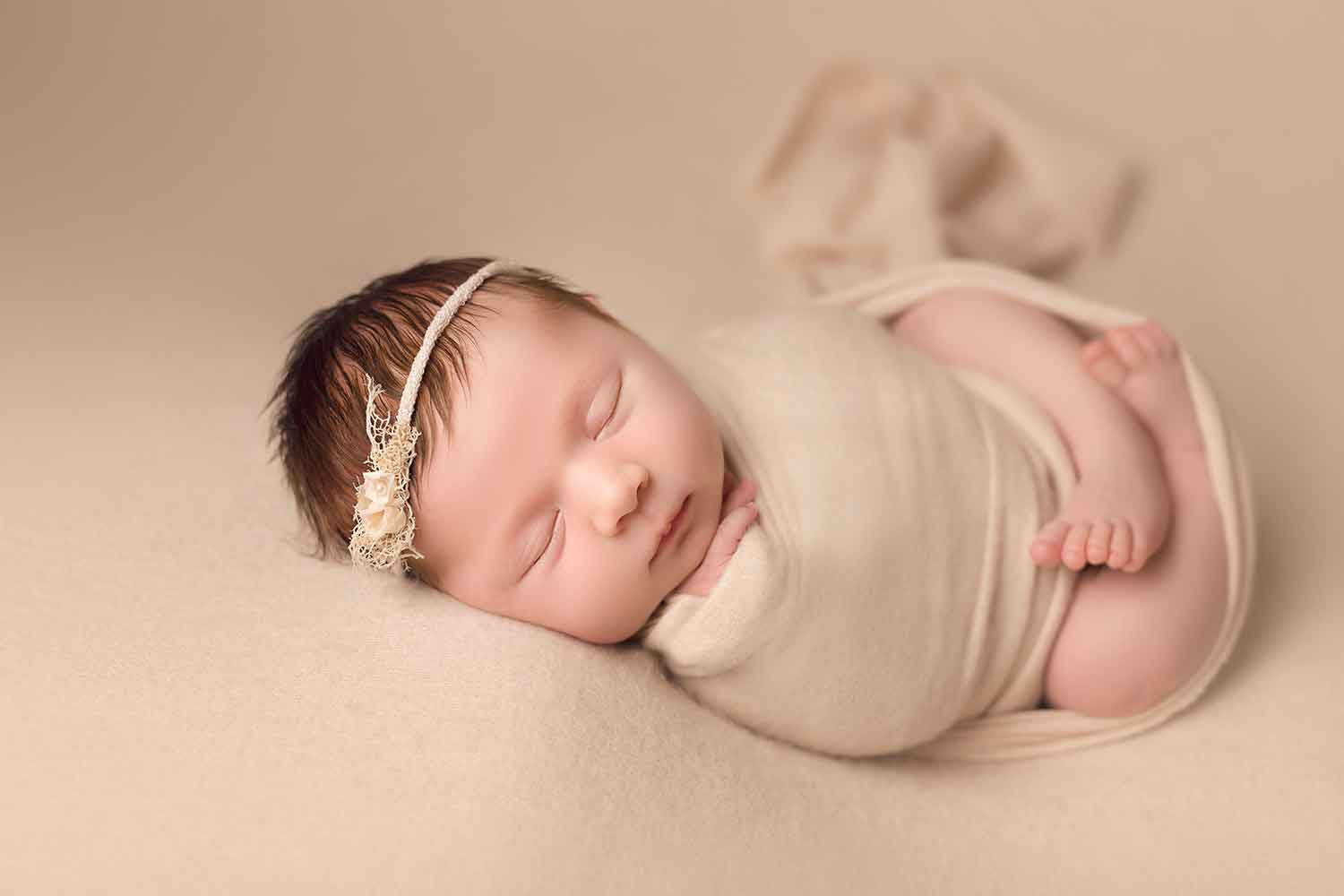 baby girl in cream wrap
