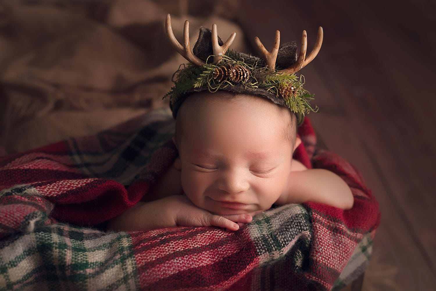 newborn baby in Christmas antler set up
