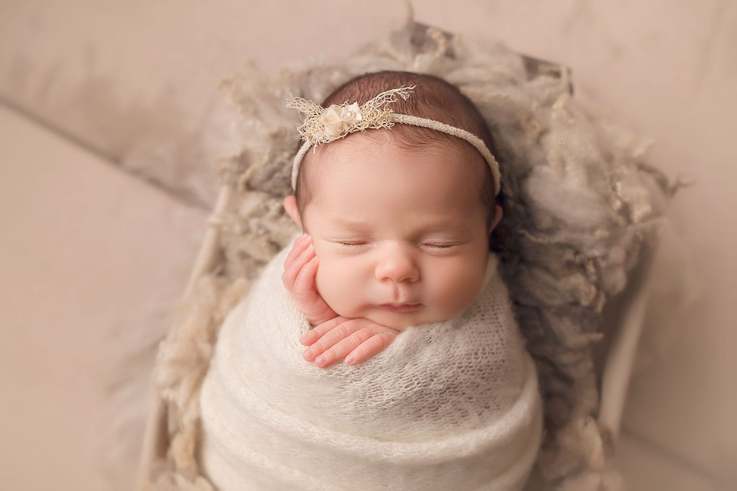 Beautiful newborn girl in cream wrap by Annie Whitaker Photography