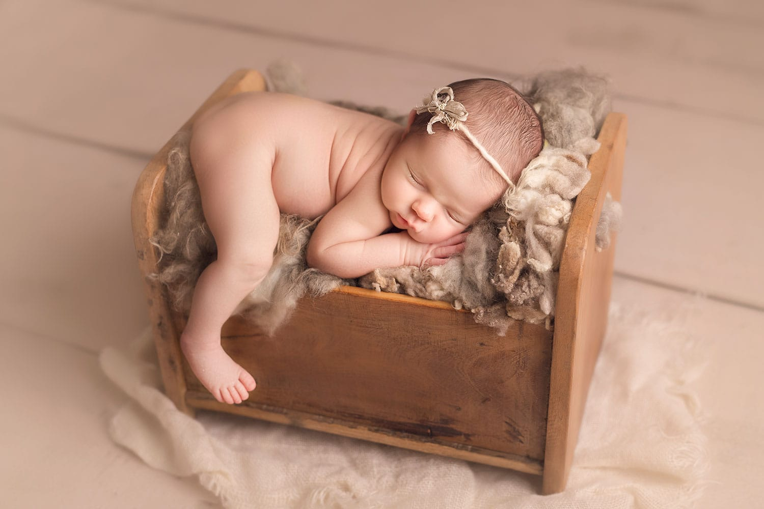 Newborn sleeping in tiny bed by Annie Whitaker Photography