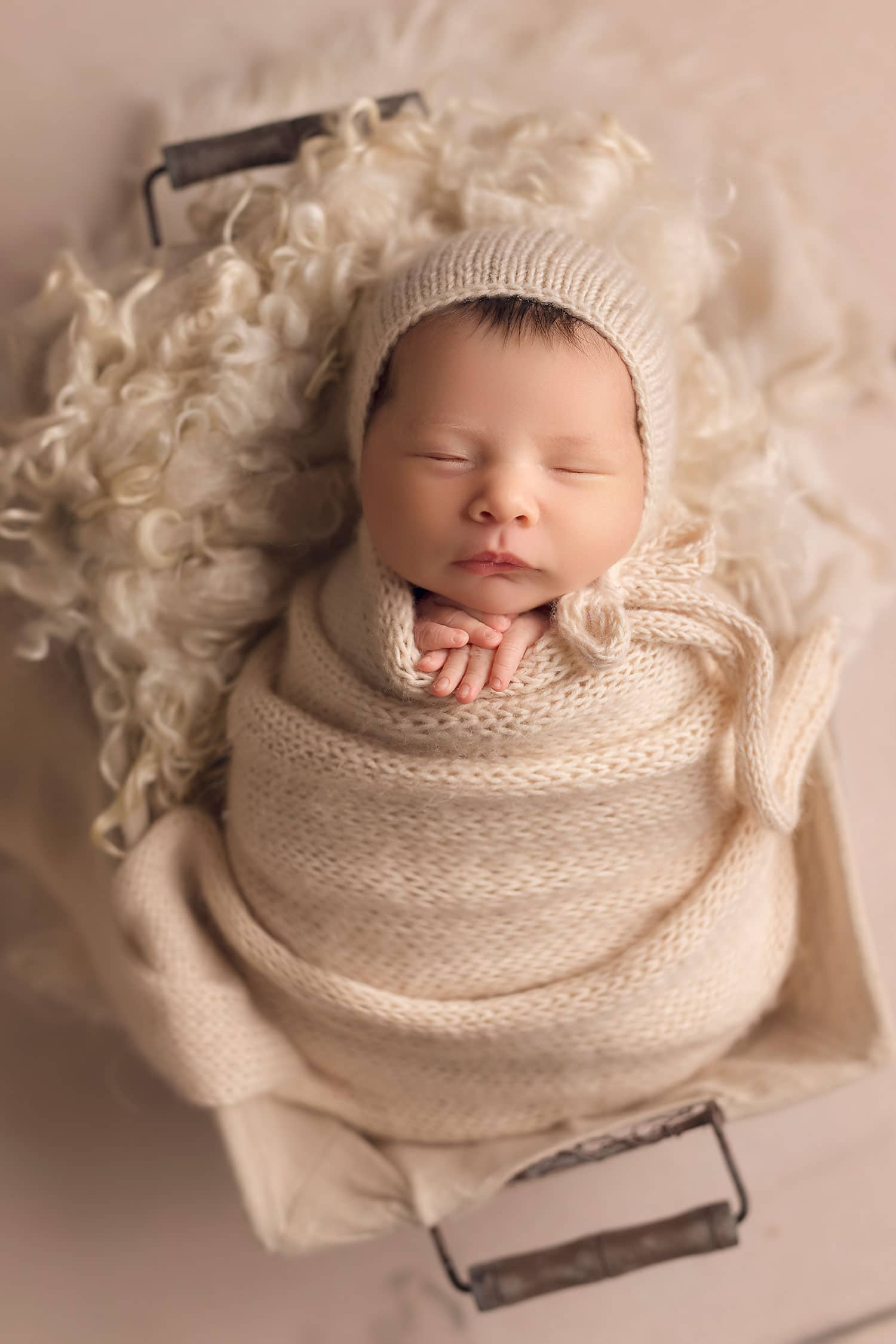 newborn baby girl in bonnet and wrap in basket by Annie Whitaker Photography
