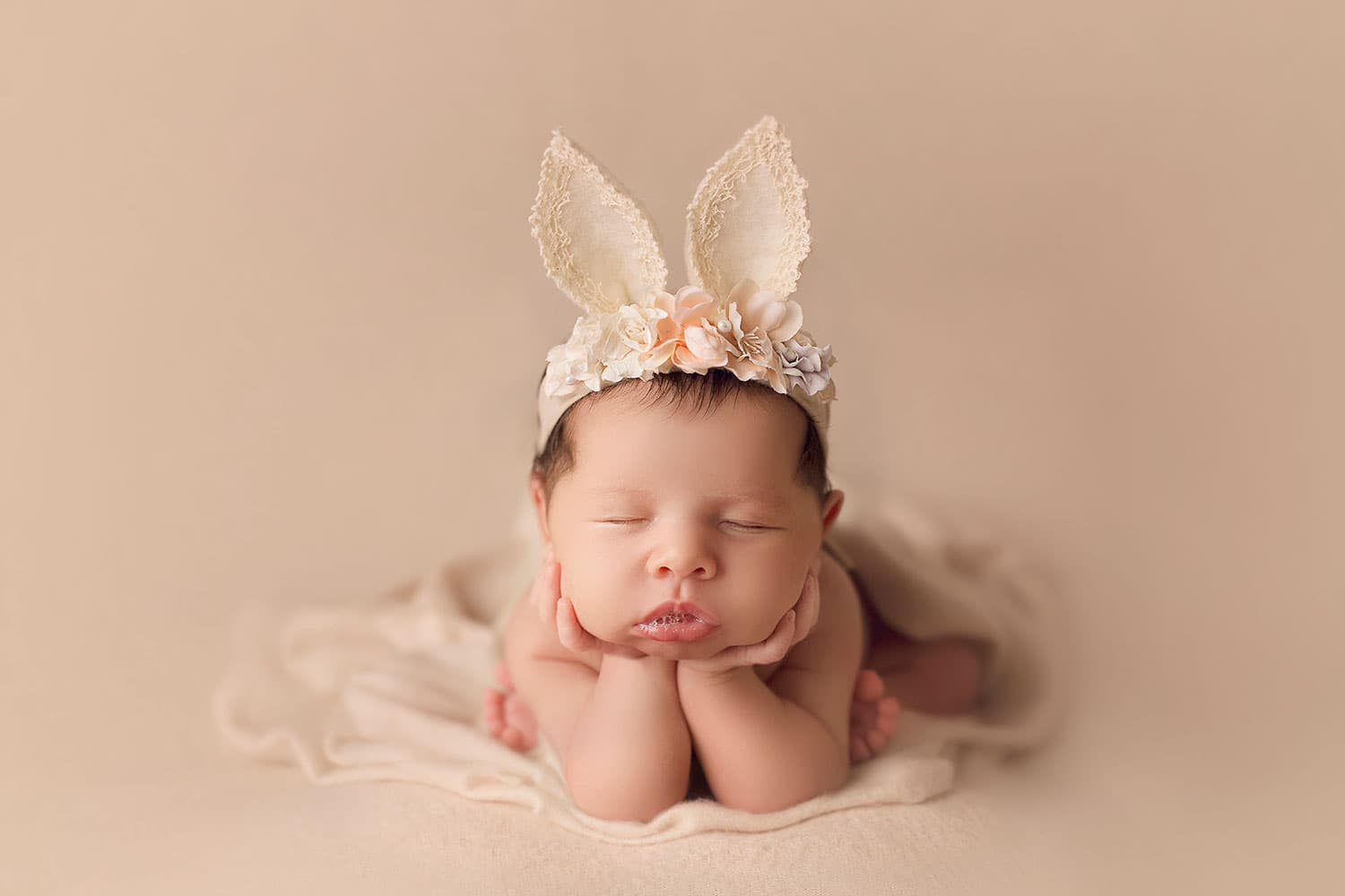 Newborn baby in bunny ear headband by Annie Whitaker Photography