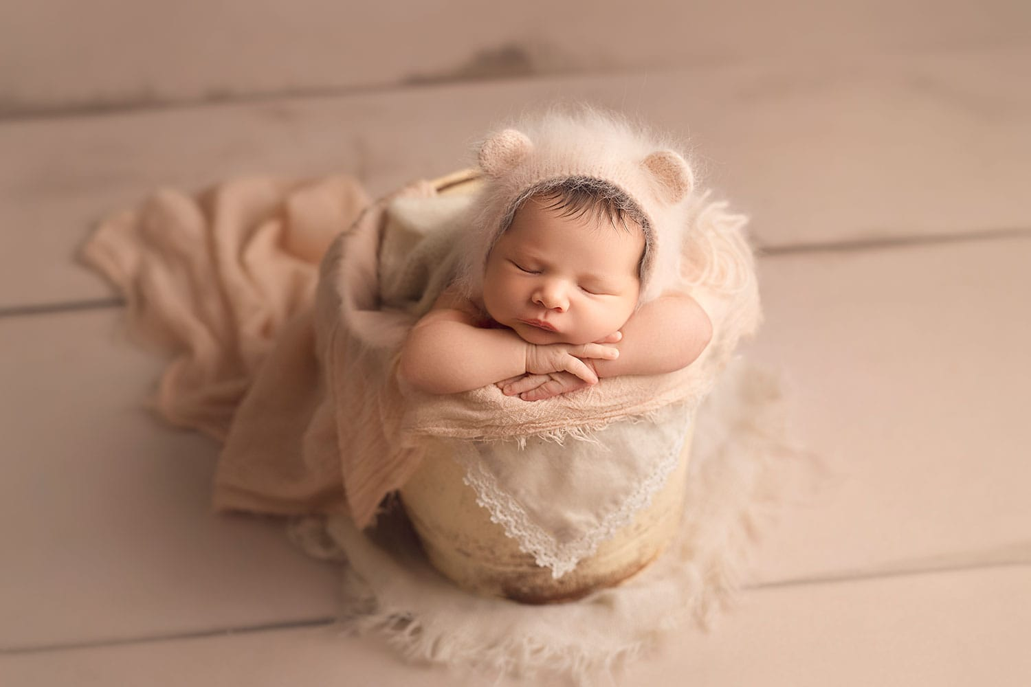 Newborn in bucket wearing bear bonnet by Annie Whitaker Photography