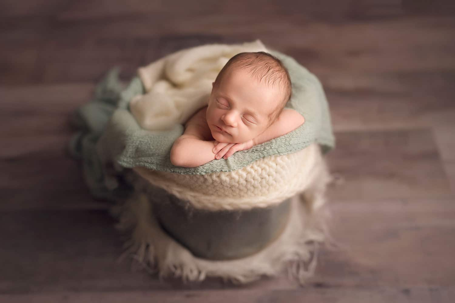 Newborn baby boy in bucket by Annie Whitaker Photography