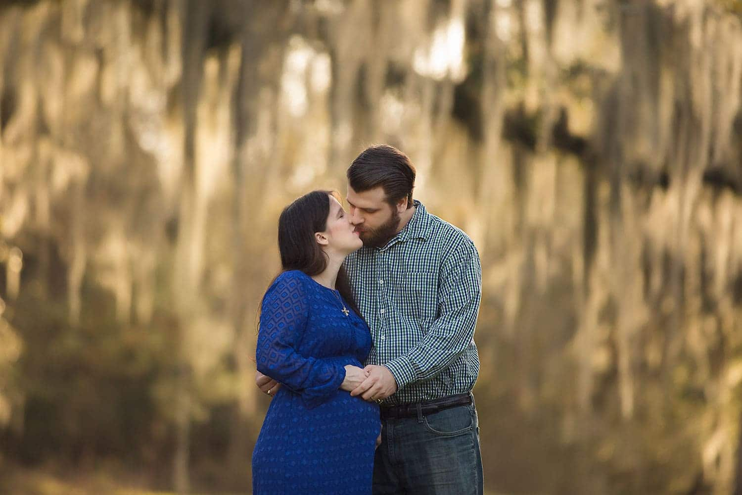 mother and father to be under mossy oak trees by Annie Whitaker Photography