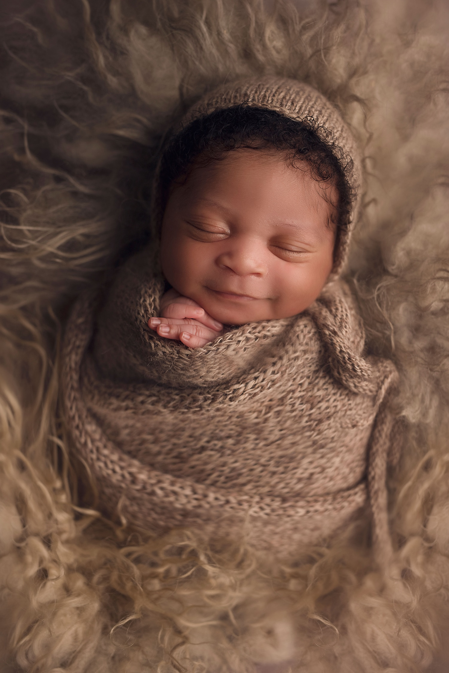 newborn baby boy smiling in brown wrap