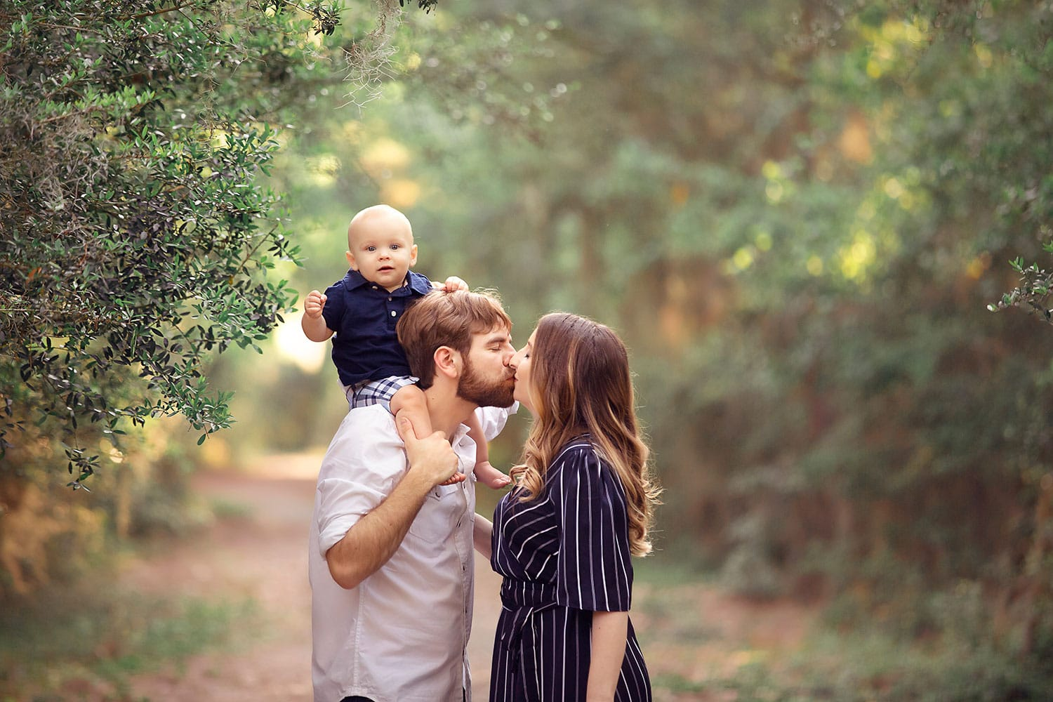 Mom and dad giving a kiss with baby on dad's shoulders by Annie Whitaker Photography