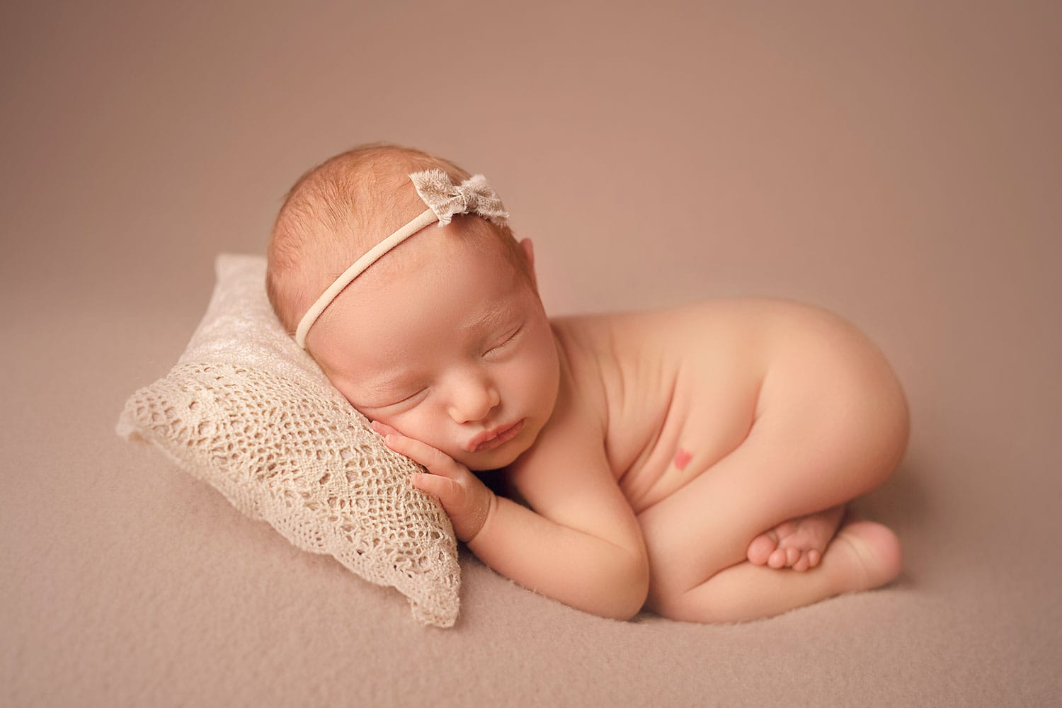 Baby girl in bum up pose with lavender & moss pillow by Annie Whitaker Photography
