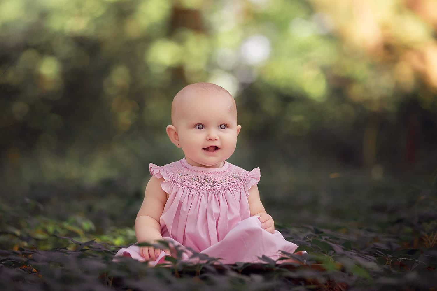smiling baby girl in pink dress by Annie Whitaker Photography