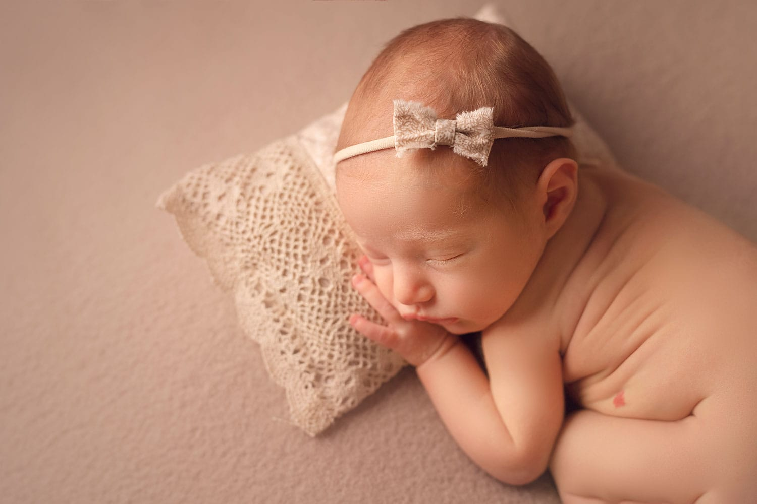 newborn baby on tiny pillow by Annie Whitaker Photography