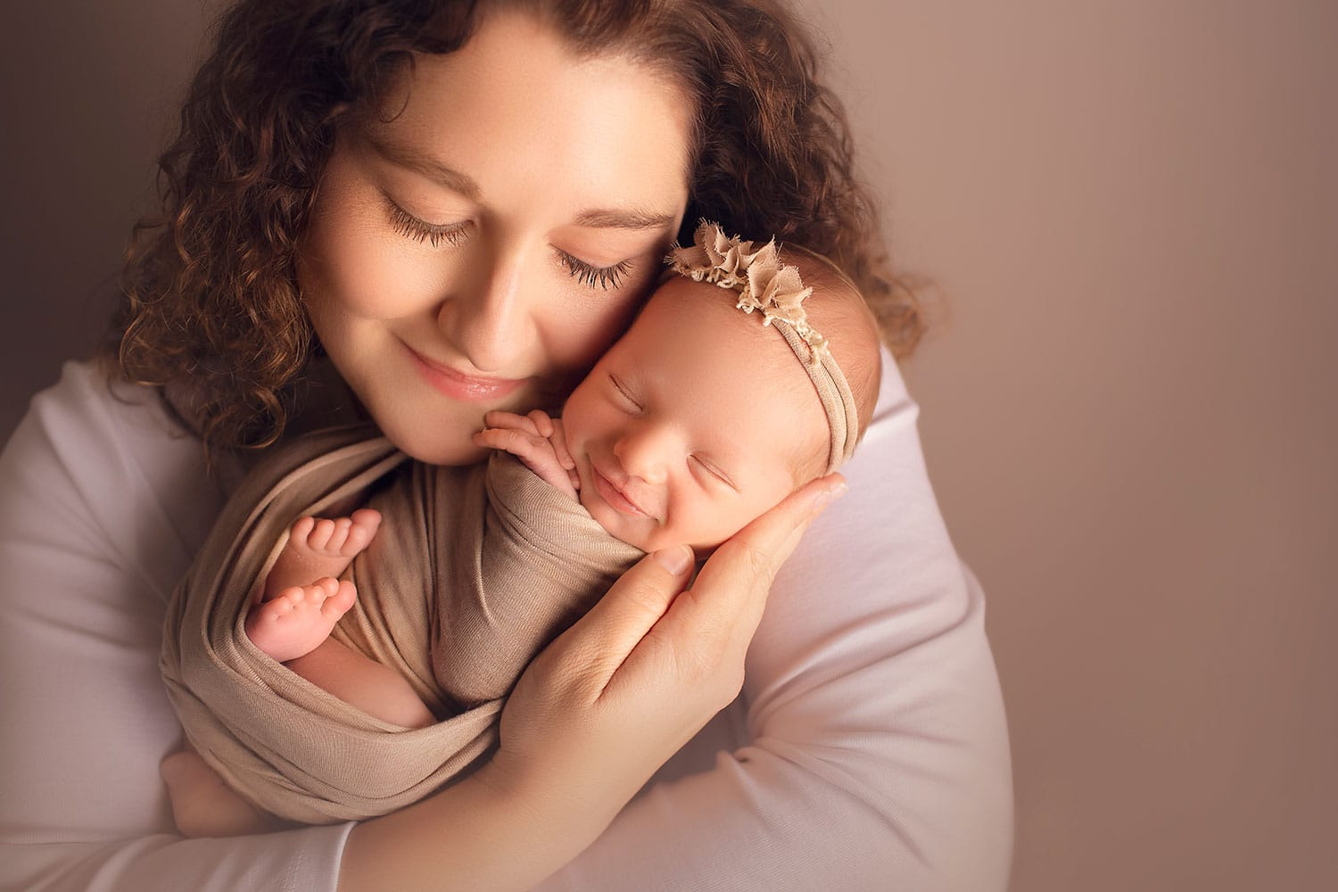 Newborn girl smiling in mom's arms by Annie Whitaker Photgraphy