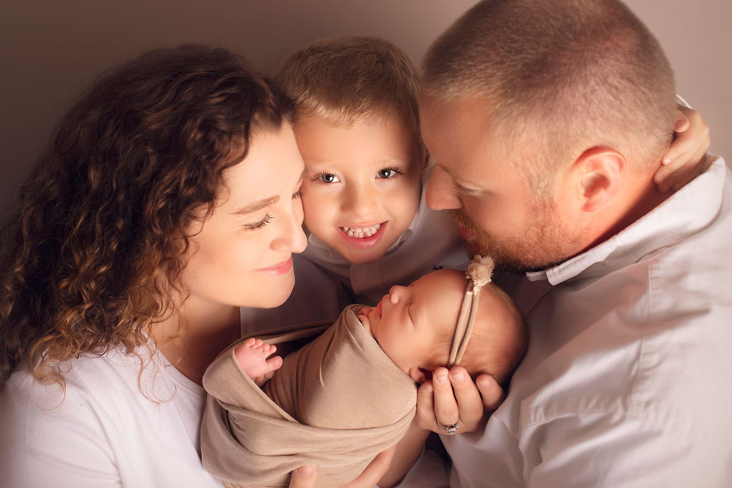 family photo with big brother smiling over newborn sister by Annie Whitaker Photography