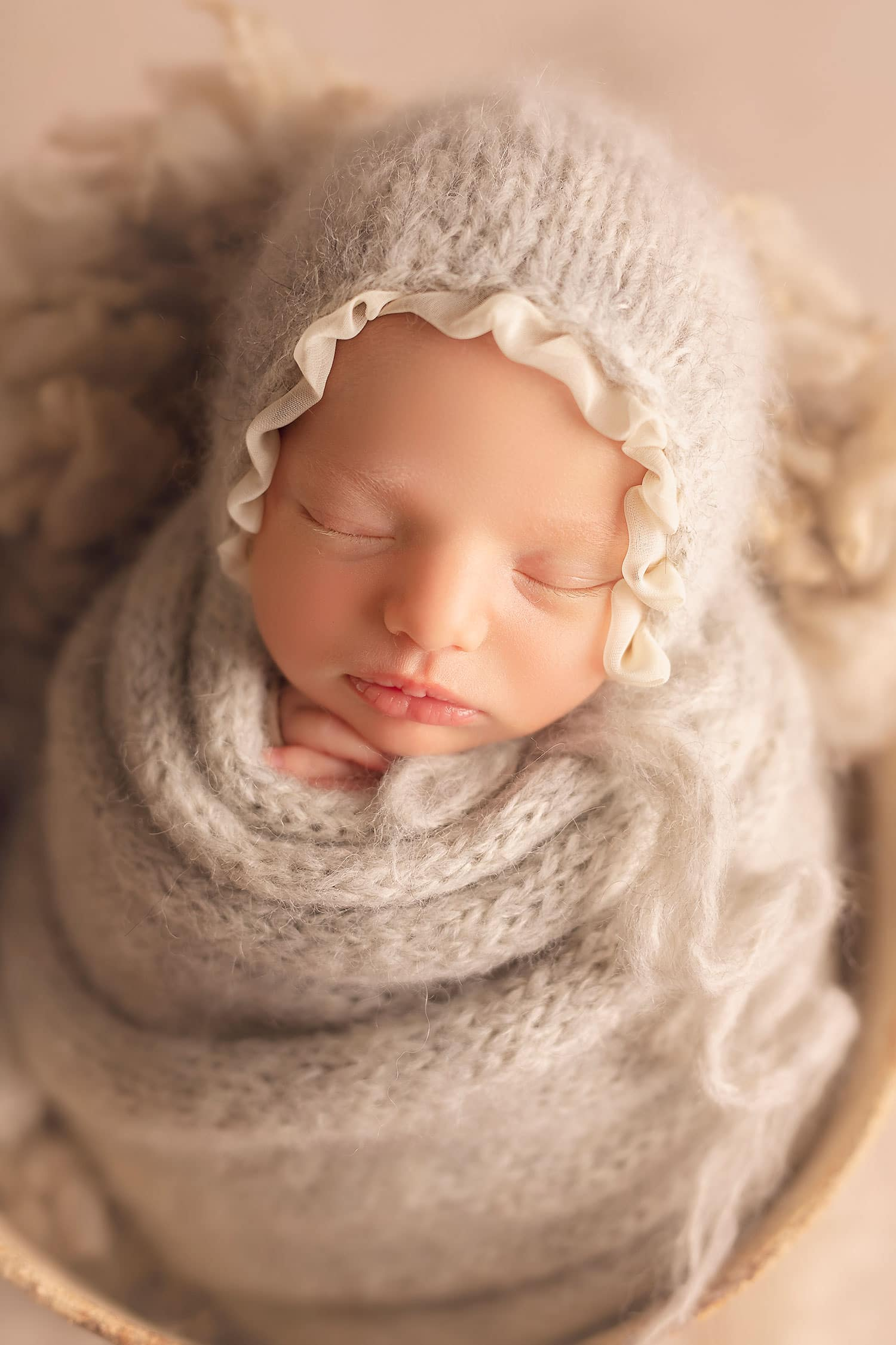 Baby girl in grey bonnet and grey wrap by Annie Whitaker Photography