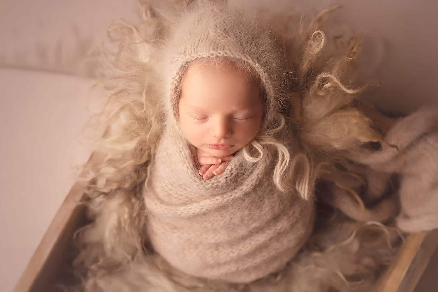 Newborn baby girl in tan wrap on Cwtchicoo fluff by Annie Whitaker Photgraphy