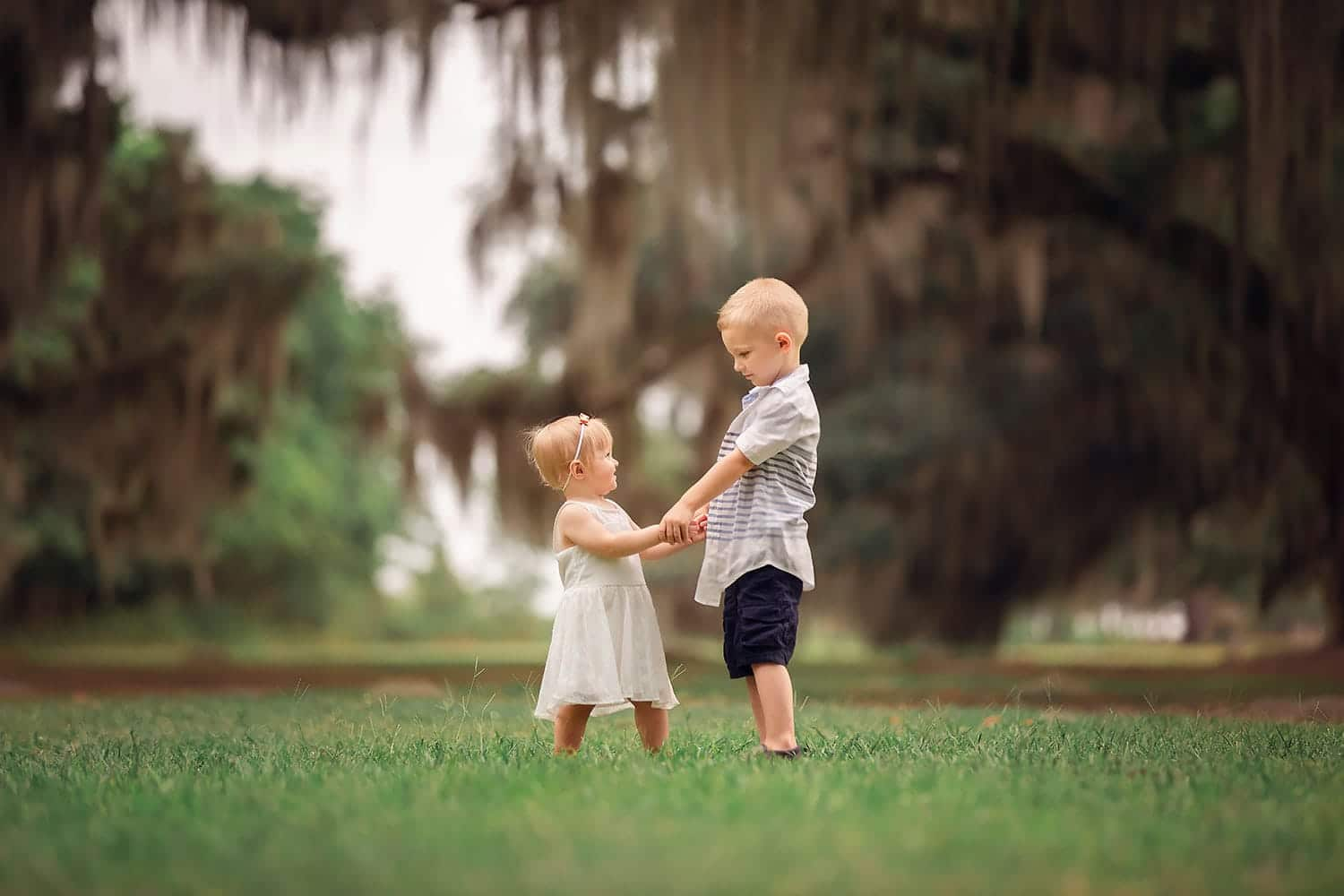 brother and sister holding hands by Annie Whitaker Photography