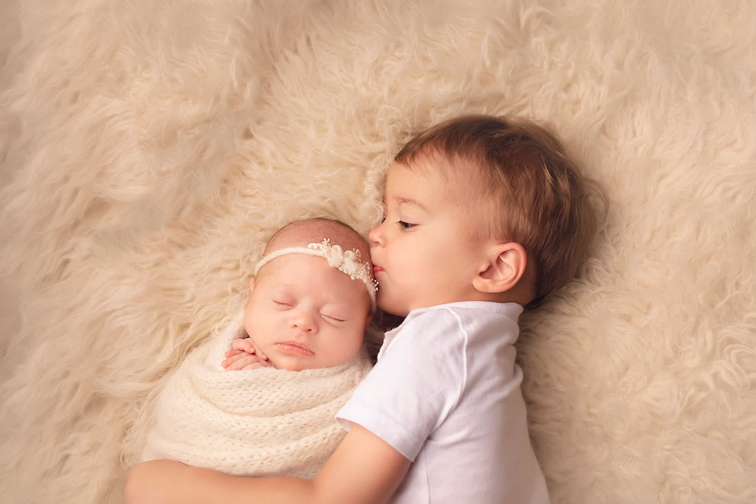 toddler brother kissing sister by Annie Whitaker Photography