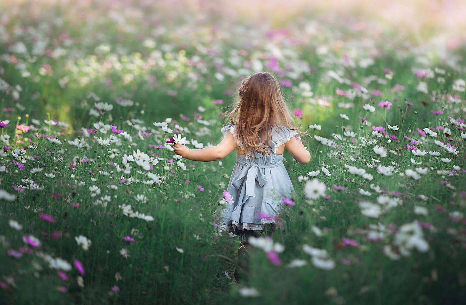 Girl running in wild flowers by Annie Whitaker Photography
